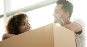 Portrait of the newlyweds near the box with things for moving. Close-up of the newlyweds near the box with things for moving. Concept of family happiness Stock Image