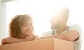 Portrait of the newlyweds near the box with things for moving. Close-up of the newlyweds near the box with things for moving. Concept of family happiness Royalty Free Stock Photography