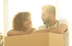Portrait of the newlyweds near the box with things for moving. Stock Image