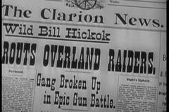 Close-up of newspaper headline Gang Broken Up in Epic Gun Battle stock video footage