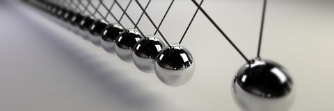 Newton cradle, cause and effect concept, steel infinity Newton`s cradle banner. Close up of a Newton`s cradle stock photos