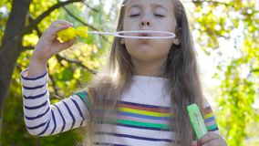 Close-up of a nice brunette girl staying in autumn sunrays and blowing soap bubbles. Little child in striped jacket. Playing in the park stock footage