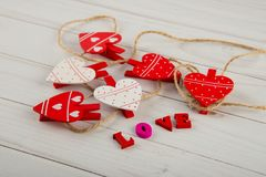 Close up on nice wooden clothespins in shape of hearts in rope laying on white table near word LOVE written by small letters royalty free stock photos