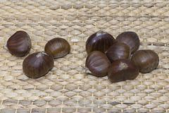 Close-up of nine raw sweet chestnuts. On a rustic  wicker basket Royalty Free Stock Images