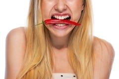 Close up no adolescente que guarda a pimenta de pimentão vermelho na boca Foto de Stock Royalty Free