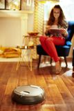 Close up no assoalho da limpeza do vácuo do robô quando mulher que relaxa imagem de stock