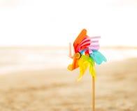 Close up no brinquedo colorido do moinho de vento na praia Fotografia de Stock