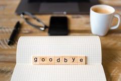 Close up no caderno sobre o fundo de madeira da tabela, foco em blocos de madeira com as letras que fazem adeus a palavra Imagens de Stock