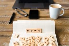 Close up no caderno sobre o fundo de madeira da tabela, foco em blocos de madeira com as letras que fazem a palavra da notícia Fotos de Stock