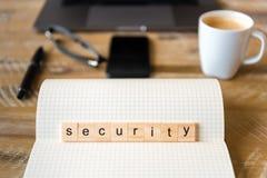 Close up no caderno sobre o fundo de madeira da tabela, foco em blocos de madeira com as letras que fazem a palavra da segurança Fotografia de Stock Royalty Free