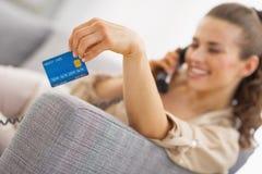 Close up no cartão de crédito à disposição do telefone de fala da jovem mulher Imagem de Stock