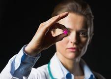 Close up no comprimido à disposição da mulher do doutor no fundo preto fotografia de stock