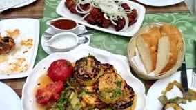 Close-up No espeto cozinhados com as cebolas com vegetais e os cogumelos grelhados na tabela no restaurante filme