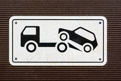 Close up no parking sign. Closeup of sign forbidding parking with tow truck on it on dark background Stock Images