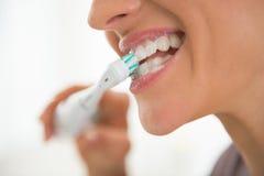 Close up nos dentes de escovadela da jovem mulher imagem de stock royalty free