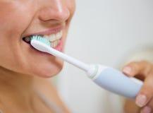 Close up nos dentes de escovadela da mulher imagens de stock