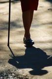 Close-up nos pés de uma senhora idosa que usa um bastão Fotos de Stock