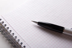 Close up of note book with checked pages and pen Royalty Free Stock Photo