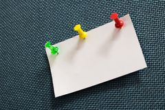 Close-up note paper and many colors pushpin into blue corkboard royalty free stock images