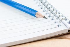 Close-up notebook and blue pencil on wood table. Close-up notebook and pencil on wood table Stock Image