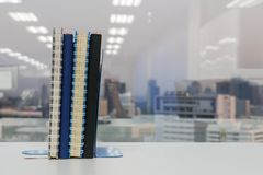 Notebook with bookend on shelf in office Stock Image