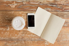 Close up of notebook, coffee cup and smartphone. Business, education, objects and technology concept - close up of notebook, coffee paper cup and smartphone on Royalty Free Stock Photo