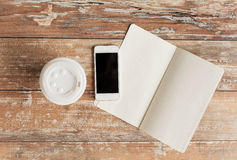 Close up of notebook, coffee cup and smartphone Royalty Free Stock Photos