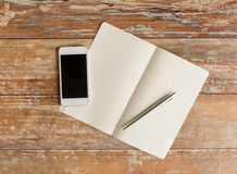 Close up of notebook, pen and smartphone. Business, education, objects and technology concept - close up of notebook, pen and smartphone on table Royalty Free Stock Photo