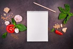 Close-up of notebook and vegetables. Close-up of notebook, pencil, vegetables, cheese, garlic and basil on a dark table. Top view Stock Images