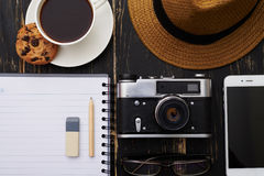 Close-up of notepad with pencil, eyeglasses, phone , hat, camera royalty free stock image