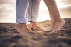 Close up of nudes couple feet for romantic and romance love concept - free people barefoot on the beach looking the sunset and