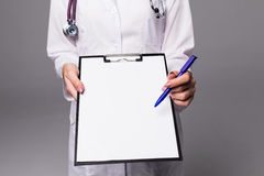 Close up Nurse pointing to clipboard on grey background royalty free stock photo