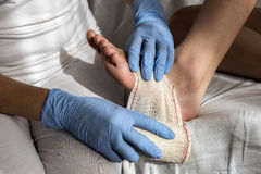 Close-up Of A Nurse Tying Bandage On Patient`s Foot Stock Images