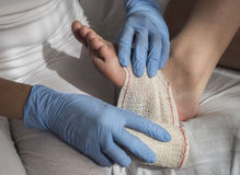 Close-up Of A Nurse Tying Bandage On Patient`s Foot Stock Photos