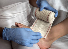 Close-up Of A Nurse Tying Bandage On Patient`s Foot Stock Photo