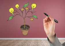 Hand holding pen and Drawing of Money and idea graphics on plant branches on wall Royalty Free Stock Images