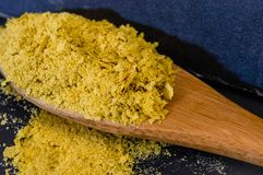 Close-up of Nutritional Yeast Flakes. Close-up of Nutritional Brewer`s Yeast Flakes on wooden spoon. High level of detail and rich texture stock image