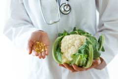 Young nutritionist holding omega pills in one hand and cauliflow in the other hand over white background. royalty free stock images