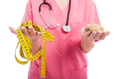 Close-up of nutritionist lady holding measuring tape and cookies. Like choosing concept isolated on white background Royalty Free Stock Photography