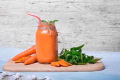 Close-up of a nutritious vitamin cocktail. Big mason jar filled with thick carrot beverage on a gray table background. Stock Photos