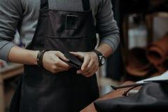 Close-up O mestre na produção de produtos da pele realiza em ruky uma bolsa Foto de Stock