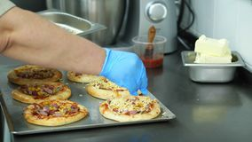 Close-up, o processo de cozinhar diverso a mini pizza da massa de fermento, com salsicha e queijo O cozinheiro chefe polvilha a p filme