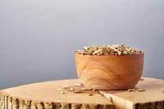 Close-up oat groats heaped in a wooden bowl on wooden log, selective focus. Close-up oat groats heaped in a wooden bowl on a wooden log over grey studio Stock Image