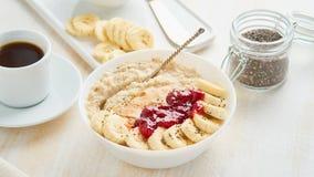 Close up of oatmeal porridge, healthy vegan diet breakfast with strawberry jam, peanut butter, banana, chia on white wooden light stock image