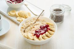 Close up of oatmeal porridge, healthy vegan diet breakfast with strawberry jam, peanut butter, banana, chia on white wooden light stock photography