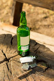 Close-up of objects - symbols of addictive habits. A bottle of alcoholic beverage, a brown cigarette, a syringe and a liighter Royalty Free Stock Images
