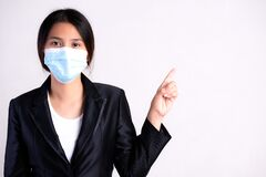 Free Close Up Of A Businesswoman In A Suit Wearing Protective Face Mask Pointing To Free Space, Get Ready For Coronavirus And Pm 2.5 Stock Photography - 177085612