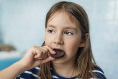 Free Close Up Of A Girl Eating A Round Chocolate Cookie Sitting In The Kitchen At Home. Harmful But Delicious Food. Sweetness Stock Photo - 183021870