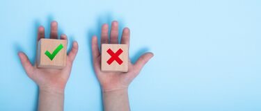 Free Close-up Of A Hands Placing Two Wooden Blocks On A Blue Background. True And False Symbols Accept Rejected For Evaluation, Yes Or Royalty Free Stock Photo - 176491875