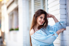 Close-up Of Attractive Brunette Girl With Long Hair Standing Near Cafe. She Wears Blue Blouse With Open Shoulders Stock Photo